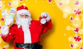 拿着触发器和闹钟的圣诞老人 库存照片