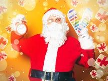 拿着触发器和闹钟的圣诞老人 免版税图库摄影