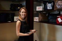 拿着触摸板的一名微笑的女实业家的半身画象,当站立与妇女的袋子的近的架子在销售中时 库存图片
