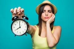 拿着警报手表的哀伤的妇女显示8时钟隔绝了在绿色背景的画象 免版税库存照片