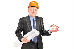 拿着计划和一个式样房子的成熟建筑师 免版税库存照片