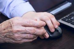 拿着计算机老鼠的一只年长妇女和男孩的手的手 免版税库存图片