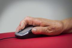 拿着计算机老鼠的风湿性关节炎手 库存图片