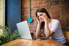 拿着计算机,膝上型计算机片剂屏幕的哀伤的妇女看起来惊奇在咖啡店 免版税图库摄影