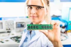 拿着记忆模块的年轻女性电子工程师手中 库存照片