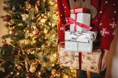 拿着许多圣诞节礼物盒的手在金黄美丽的chri 库存照片