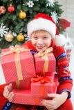 拿着许多红色礼物的小孩用金黄ribbo装饰 图库摄影