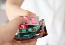 拿着许多药片的药剂师 免版税库存照片
