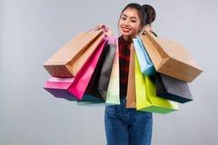 拿着许多袋子的购物的愉快的亚裔妇女 隔绝在灰色背景黑星期五假日 复制空间为 库存图片