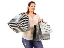 拿着许多购物袋的微笑的妇女 免版税库存照片
