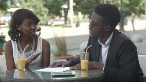 拿着论文的非裔美国人的商人,解释细节,当开会议在咖啡店时 股票录像