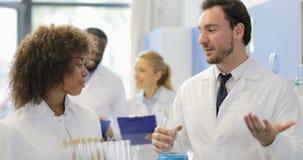 拿着试管和烧瓶有化学制品的男性和女性科学家谈在现代实验室 股票录像