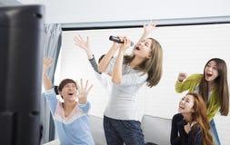 拿着话筒和唱歌在卡拉OK演唱的妇女 免版税库存照片
