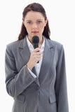 拿着话筒的一名严重的女实业家 库存照片