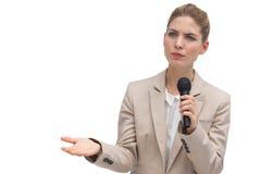 拿着话筒的皱眉的女实业家 免版税库存图片