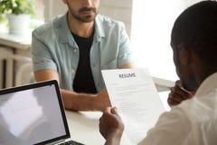 拿着读书申请人的非裔美国人的hr经理恢复在 免版税库存照片