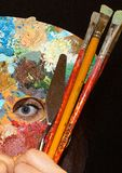拿着调色板和看通过它的俏丽的年轻女人是孔 库存照片
