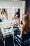 拿着调色板的年轻专业visagiste应用眼影膏于在美容院的白种人女性模型 库存照片