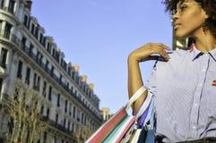 拿着购物带来的美丽的年轻黑人妇女 关于购物、生活方式和人的概念 库存图片