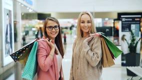 拿着购物带来的美女画象在看照相机和微笑的大商店 年轻女人佩带 股票录像