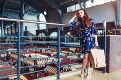 拿着购物的纸袋和等待朋友的年轻愉快的妇女在购物中心 库存照片