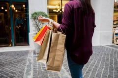 拿着购物袋的妇女,当走在葡萄酒街道,商店上时 图库摄影