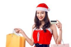 拿着购物袋的微笑的妇女在显示cre的圣诞节前 库存图片