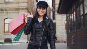 拿着购物袋的愉快的亚裔女孩慢动作画象,回家从然后转动和看的商店 影视素材