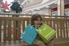 拿着购物袋的愉快的女孩在购物中心 库存照片