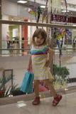 拿着购物袋的愉快的女孩在购物中心 免版税库存图片
