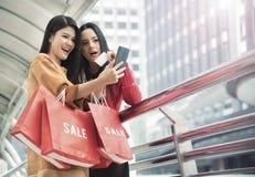 拿着购物袋的美丽的女孩使用一个巧妙的电话 免版税图库摄影