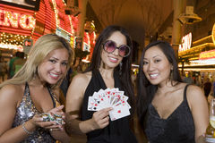 拿着赌博娱乐场芯片、纸牌和香宾瓶的妇女 免版税库存图片