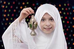拿着赖买丹月灯笼的白色Hejab的年轻回教女孩 免版税库存照片