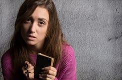 拿着赞美诗书和十字架的年轻基督徒妇女 免版税库存图片