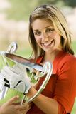 拿着赢取的战利品的女性高尔夫球运动员 免版税库存照片