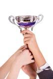 拿着赢取的杯子的人们 库存图片