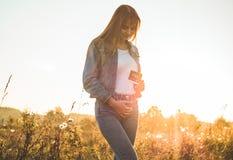 拿着超声波照片在日落和拥抱她的腹部的年轻人孕妇 4个月怀孕 产科概念 被定调子的照片 免版税库存图片