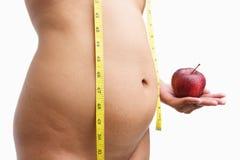 拿着超重妇女的苹果机体 图库摄影