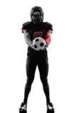 拿着足球剪影的美国橄榄球运动员 免版税图库摄影