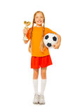 拿着足球和奖的小白肤金发的女孩 免版税库存照片
