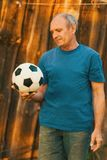 拿着足球的一个年长人 免版税图库摄影
