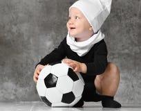拿着足球的婴孩的逗人喜爱的图象 免版税库存图片