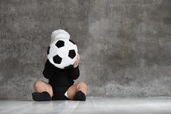 拿着足球的婴孩的逗人喜爱的图象 免版税库存照片