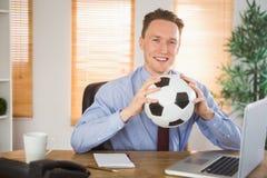 拿着足球的快乐的商人 免版税库存图片