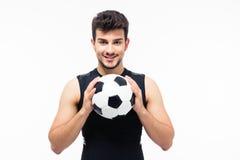 拿着足球的愉快的足球运动员 库存照片