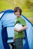 拿着足球的男孩反对帐篷 免版税库存图片