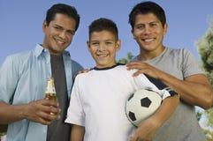 拿着足球的男孩(13-15)站立与两个兄弟举行啤酒瓶正面图的一个兄弟。 免版税库存图片