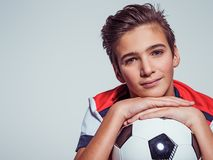 拿着足球的运动服的微笑的青少年的男孩 免版税库存图片