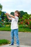 拿着跨越横线的愉快的男孩画象 库存图片