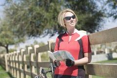 拿着路线图的自行车骑士,当倾斜在篱芭时 免版税库存照片